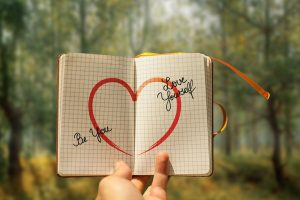 """A notebook with a heart drawn on it and words saying """"Be You"""" and """"Love Yourself"""""""